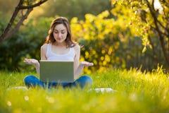 有膝上型计算机的妇女在运作在公园的莲花姿势 免版税库存图片