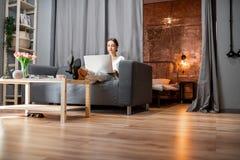 有膝上型计算机的妇女在长沙发在家 免版税图库摄影