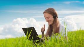 有膝上型计算机的妇女在绿色草甸 股票视频