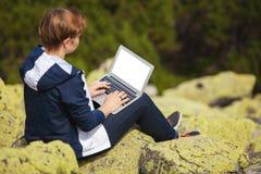 有膝上型计算机的妇女坐石头 免版税库存照片