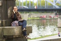 有膝上型计算机的妇女户外谈话坐电话 愉快 库存照片