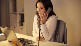 有膝上型计算机的妇女拜访电话的在夜办公室 影视素材
