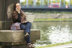 有膝上型计算机的妇女谈话在电话,当坐美丽的老镇时江边  免版税库存照片