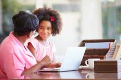 有膝上型计算机的孙女帮助的祖母 免版税库存照片
