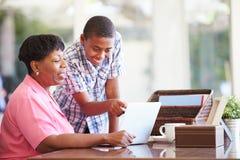 有膝上型计算机的孙子帮助的祖母 免版税库存图片