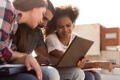有膝上型计算机的学生在校园里 库存照片