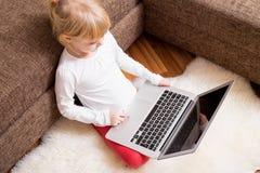 有膝上型计算机的孩子在她的膝部 库存照片
