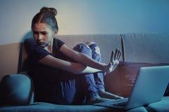 有膝上型计算机的害怕十几岁的女孩在沙发 互联网的危险 免版税图库摄影