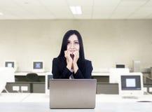 有膝上型计算机的害怕女实业家在办公室 库存图片