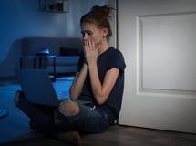 有膝上型计算机的害怕的十几岁的女孩在地板上 互联网的危险 库存图片