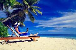 有膝上型计算机的少妇在热带海滩 图库摄影