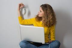有膝上型计算机的少妇拿着一只架线的计算机老鼠 免版税库存照片