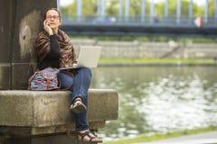 有膝上型计算机的少妇谈话在电话 免版税库存照片
