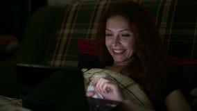 有膝上型计算机的少妇谈话在Skype,当在床上在晚上时 股票视频