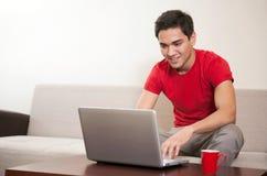 有膝上型计算机的年轻人在沙发 免版税库存图片
