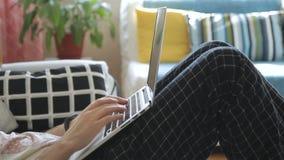 有膝上型计算机的年轻人坐沙发在客厅 股票录像