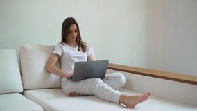 有膝上型计算机的年轻女人在沙发 研究膝上型计算机的女孩自由职业者在家 股票录像