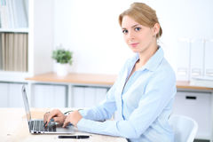 有膝上型计算机的年轻白肤金发的女商人在办公室 到达天空的企业概念金黄回归键所有权 库存照片