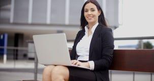 有膝上型计算机的微笑的女工在长凳 库存图片