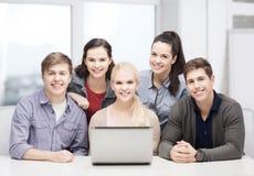 有膝上型计算机的微笑的学生在学校 免版税库存图片