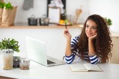 有膝上型计算机的微笑的少妇在厨房里在 图库摄影