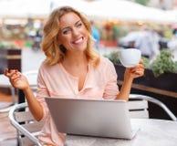 有膝上型计算机的微笑的少妇 免版税库存照片