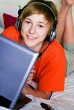 有膝上型计算机的微笑的少年 图库摄影