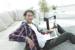 有膝上型计算机的微笑的年轻人坐地板在长沙发附近 库存图片