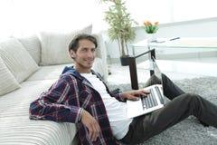 有膝上型计算机的微笑的年轻人坐地板在长沙发附近 库存照片