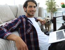 有膝上型计算机的微笑的年轻人坐地板在长沙发附近 免版税图库摄影