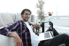 有膝上型计算机的微笑的年轻人坐地板在长沙发附近 免版税库存照片