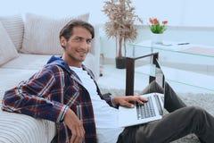 有膝上型计算机的微笑的年轻人坐地板在长沙发附近 免版税库存图片
