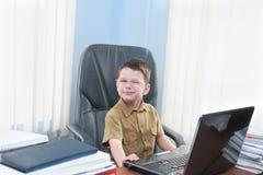 有膝上型计算机的微笑的男孩 免版税库存照片