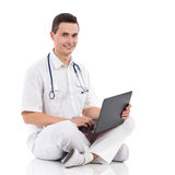 有膝上型计算机的微笑的男性医学学生 图库摄影