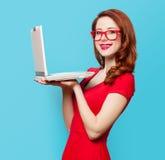 有膝上型计算机的微笑的红头发人女孩 图库摄影