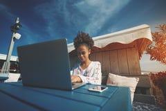 有膝上型计算机的微笑的非洲的女孩在街道咖啡馆 免版税图库摄影