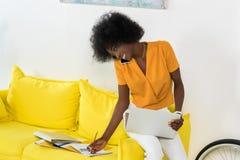 有膝上型计算机的微笑的非裔美国人的女性自由职业者谈话在智能手机,当工作在沙发时 免版税库存图片