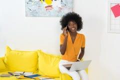 有膝上型计算机的微笑的非裔美国人的女性自由职业者谈话在智能手机,当工作在沙发时 库存图片