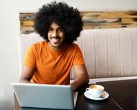 有膝上型计算机的微笑的年轻黑人在咖啡馆桌上 免版税库存照片