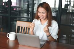 有膝上型计算机的快乐的年轻亚裔女实业家微笑在工作场所的在办公室 成功企业的概念 免版税库存图片