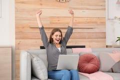 有膝上型计算机的情感年轻女人庆祝在沙发的胜利 免版税库存照片