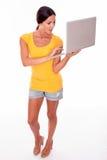 有膝上型计算机的惊奇的深色的妇女 免版税库存图片
