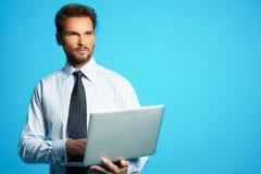 有膝上型计算机的愉快的商人-被隔绝在蓝色背景 免版税库存图片