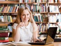 有膝上型计算机的愉快的女学生在图书馆里 免版税库存图片