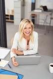 有膝上型计算机的愉快的女实业家在大角度看法 库存图片