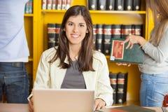 有膝上型计算机的愉快的妇女在大学图书馆 图库摄影