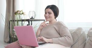有膝上型计算机的愉快的妇女在沙发 影视素材