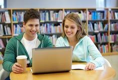 有膝上型计算机的愉快的学生在图书馆里 库存图片