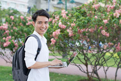 有膝上型计算机的愉快的微笑的大学生 免版税库存图片