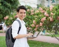 有膝上型计算机的愉快的微笑的大学生 免版税库存照片